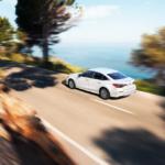 A white 2022 Civic Sedan driving along a beach or ocean road