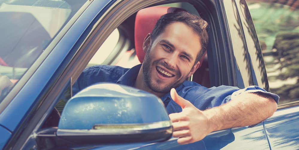 Man Giving a Thumbs Up in a Used Car
