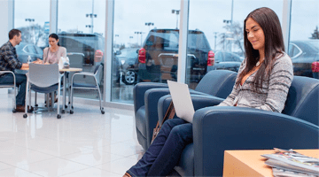 A girl sitting inside a dealership, looking at her computer.