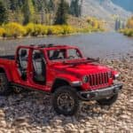 Image of a red 2020 Jeep Gladiator parked near a stream.